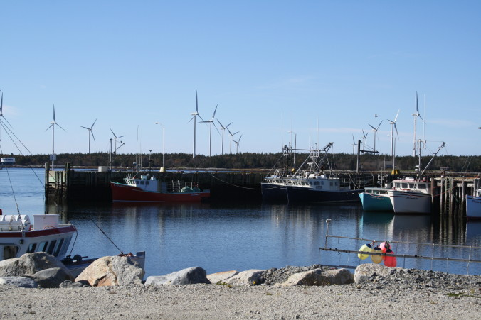 Pubnico wind turbines behind fishing boats.